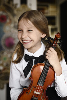Portrait of a happy girl with a violin at home - EYAF00221