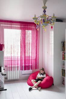 Girl reading a book in her room - EYAF00242