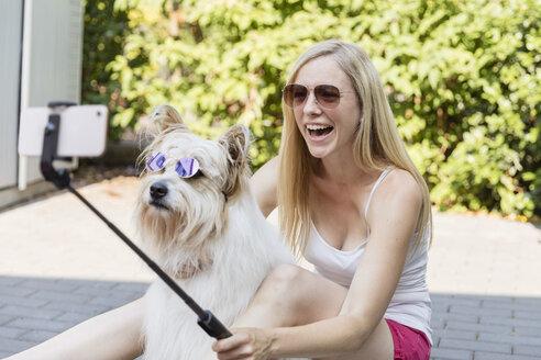 blonde Frau macht Selfies mit ihrem Hund mit Sonnenbrillen, Frankfurt, Deutschland - SHKF00806