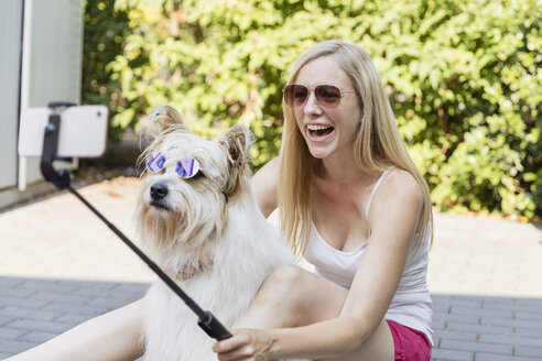 Happy woman taking a selfie with her dog wearing sunglasses - SHKF00806