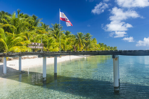 French Polynesia, Tuamotus, Tikehau, pier at palm beach with flag - RUNF02073