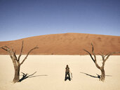 Woman standing between trees in Deadvlei, Namib desert, Namib-Naukluft National Park, Namibia - VEGF00241