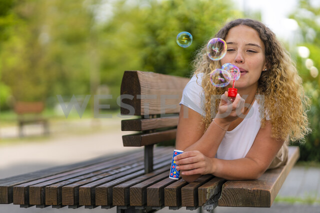Young woman lying on bench, blowing soap bubbles - STSF01982 - Stefan Schurr/Westend61
