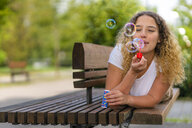 Young woman lying on bench, blowing soap bubbles - STSF01982