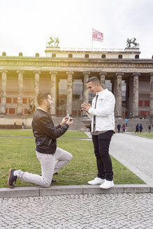 happy Homosexual couple a white caucasian and a latino in Berlin where a guy is proposing to his boyfriend - TAMF01497