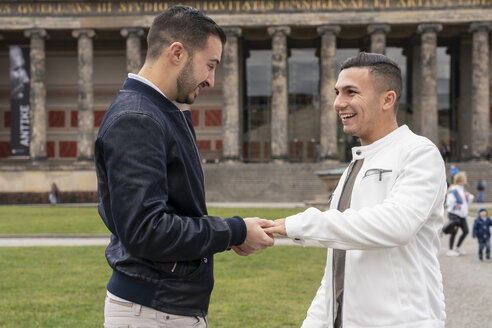 Young man putting on ring to his happy boyfriend at Lustgarten, Berlin, Germany - TAMF01500