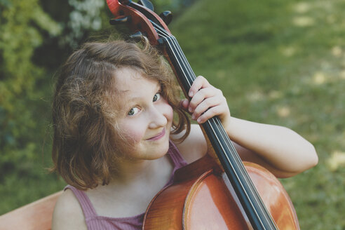 A smiling girl with the cello in garden - IHF00026