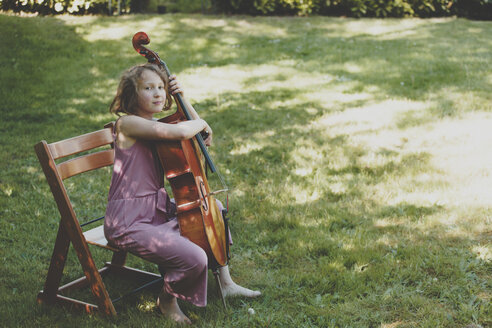 A girl playing the cello in garden, looking to camera - IHF00029