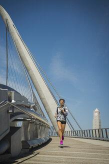 Caucasian woman running on bridge - BLEF03680