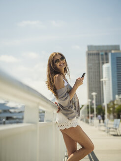 Caucasian woman leaning on railing texting on cell phone - BLEF03683
