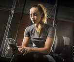 Caucasian woman texting on cell phone in gymnasium - BLEF03728