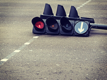 Traffic light laying in street intersection - BLEF03803