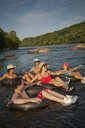Friends floating on river in inner tubes - BLEF03824
