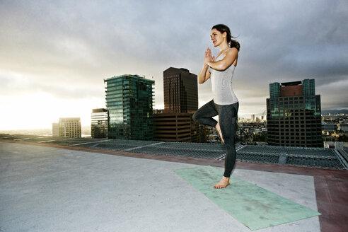 Caucasian woman doing yoga urban rooftop - BLEF03845