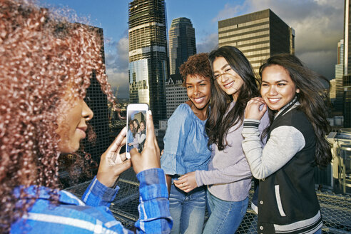 Stylish woman photographing friends on urban rooftop with cell phone - BLEF03857