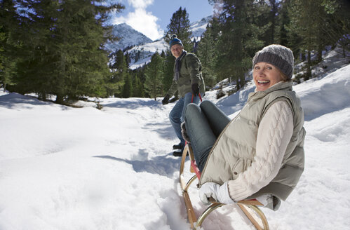 Man pulling wife on sled in snow covered wilderness - JUIF01028