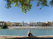 Tourist sitting on waterfront in Seville, Spain - JUIF01043