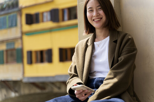 Italy, Florence, happy young woman with smartphone resting in the city - FMOF00615
