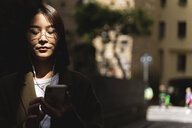 Italy, Florence, young woman with cell phone and earphones in sunlight in the city - FMOF00624
