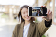 Italy, Florence, young tourist woman taking a selfie at Ponte Vecchio - FMOF00627