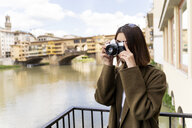 Italy, Florence, young tourist woman taking pictures at Ponte Vecchio - FMOF00630