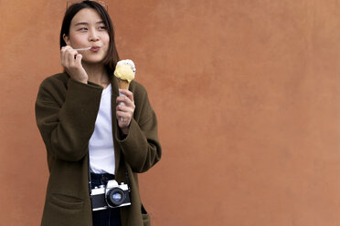 Young woman eating an ice cream cone at an orange wall - FMOF00633