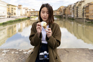 Italy, Florence, young tourist woman eating an ice cream cone at at Ponte Vecchio - FMOF00636