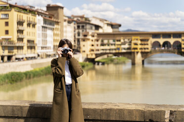 Italy, Florence, young tourist woman taking pictures at Ponte Vecchio - FMOF00642