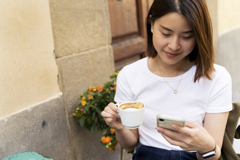 Italy, Florence, young woman using cell phone at an outdoor cafe - FMOF00654