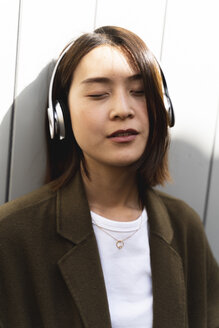 Relaxed young woman with closed eyes listening to music with headphones - FMOF00657