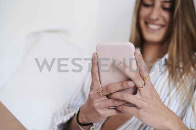 Young woman sitting on bed, using smartphone - IGGF01175 - Ivan Gener/Westend61