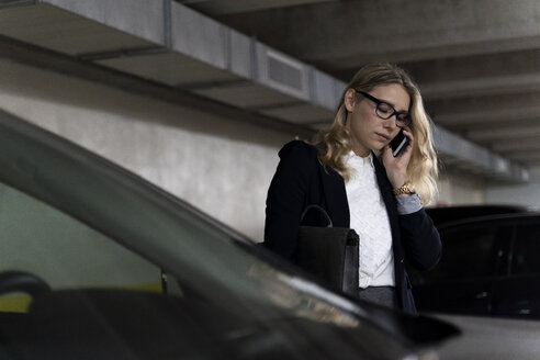 Businesswoman on the phone in car park - FMOF00661