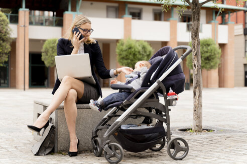 Young businesswoman with baby boy in stroller working outdoors - FMOF00673