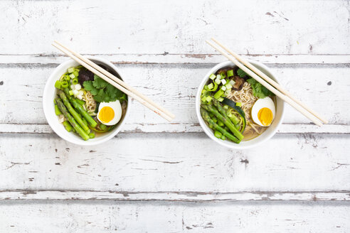 Two bowls of Ramen soup with egg, green asparagus, noodles, shitake mushroom and spring onions - LVF08048