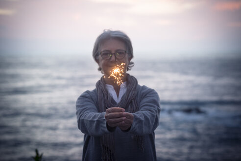 Happy senior woman standing in front of the sea by sunset holding sparkler - SIPF01980