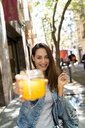 Young woman holding glass with fresh juice - AFVF02961