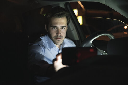 Young man using cell phone in car at night - UUF17600