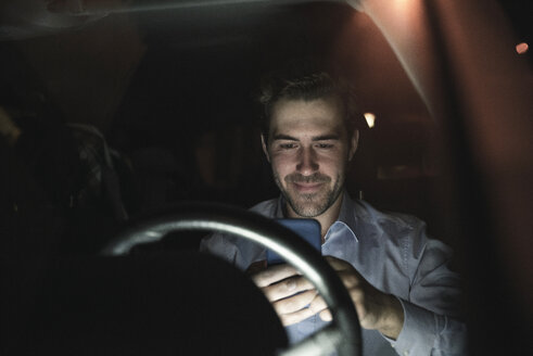 Young man using cell phone in car at night - UUF17606