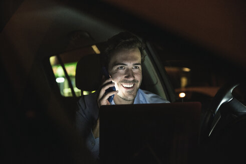 Happy young man on cell phone in car at night - UUF17612