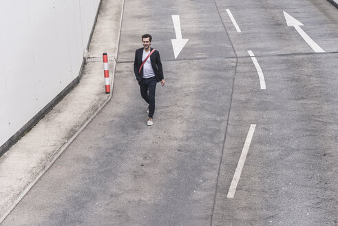 Confident businessman walking on road with arrow signs - UUF17621