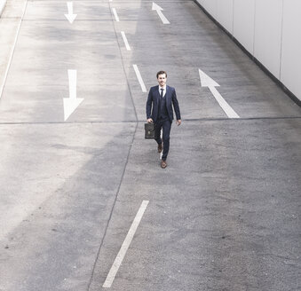 Businessman walking on road with arrow signs - UUF17642