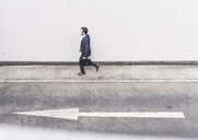 Businessman walking at road with arrow sign - UUF17645