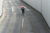 Businessman with umbrella walking on road with arrow signs - UUF17651
