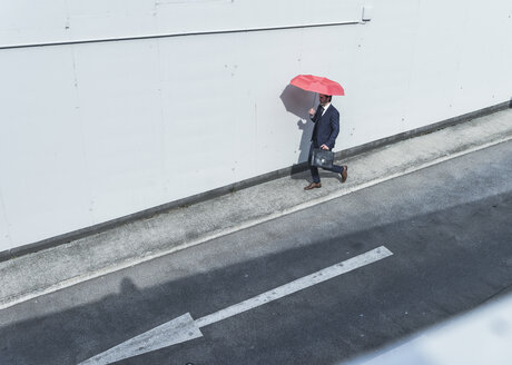Businessman with umbrella walking at road with arrow sign - UUF17654