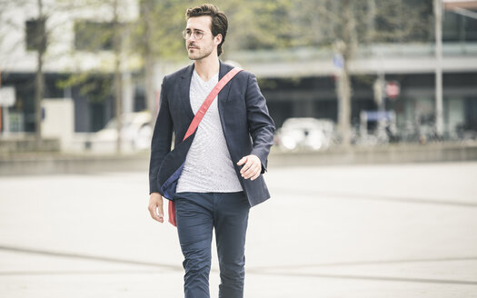 Businessman walking in the city looking around - UUF17657