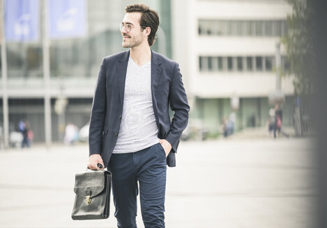 Confident businessman walking in the city - UUF17660