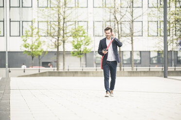 Businessman walking in the city with cell phone and earphones - UUF17663