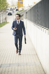 Businessman walking in the city with cell phone and earphones - UUF17672