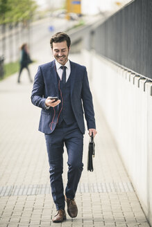 Businessman walking in the city with cell phone and earphones - UUF17675