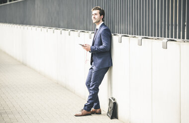 Businessman leaning against a wall in the city with cell phone and earphones - UUF17681